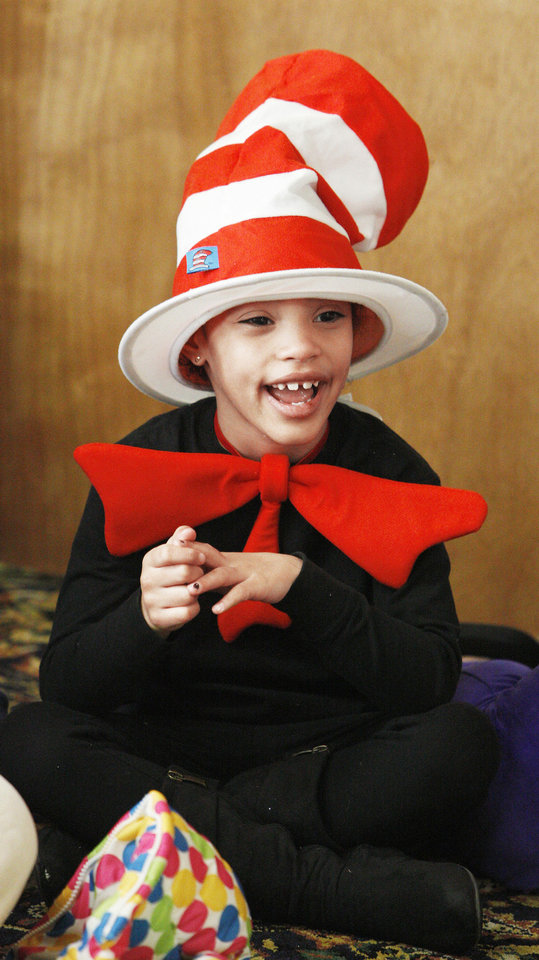 Photo - Special Care pre-K student Emma Kearney, 5, dressed in a Cat in the Hat costume as students from Positive Tomorrows and Special Care are read to at The Fountains at Canterbury as part of Read Across America Day, held close to the birthday of Dr. Seuss.  Photo by Paul B. Southerland, The Oklahoman