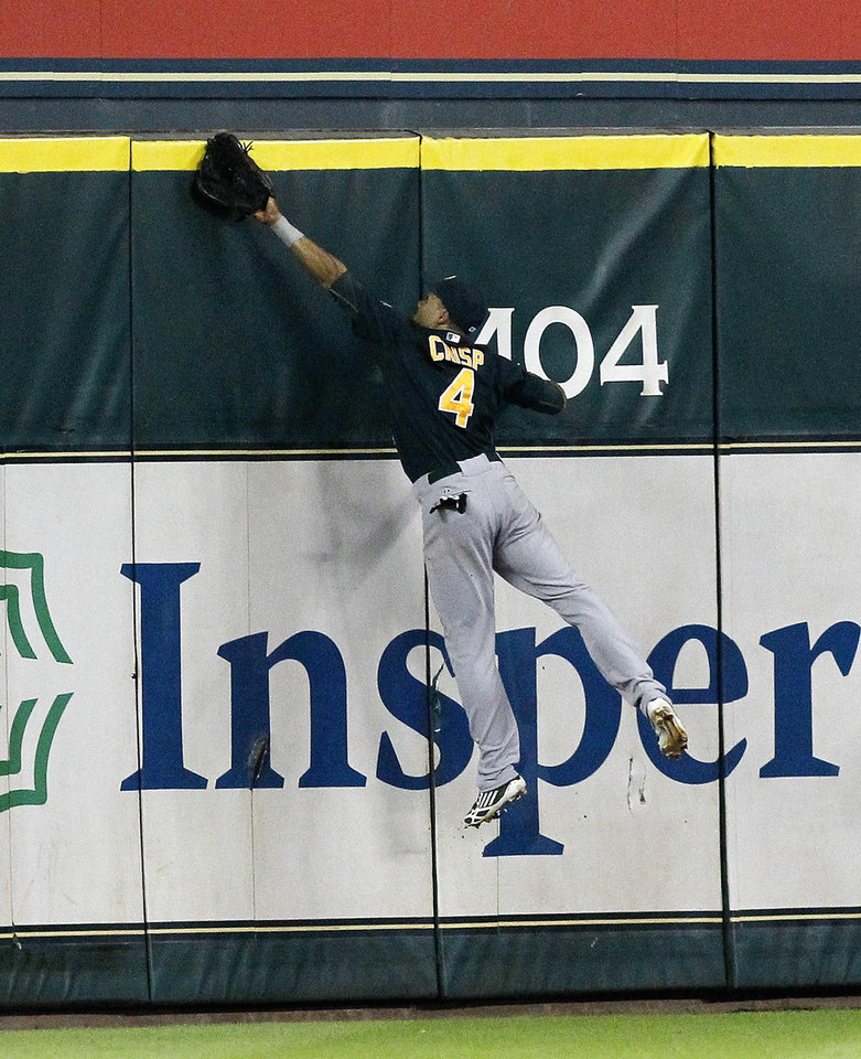 Photo - Oakland Athletics' Coco Crisp (4) leaps at the wall but can't make a catch on a home run hit by Houston Astros' Matt Dominguez in the ninth inning of a baseball game on Tuesday, July 23, 2013, in Houston. The Astros won 5-4. (AP Photo/Bob Levey)