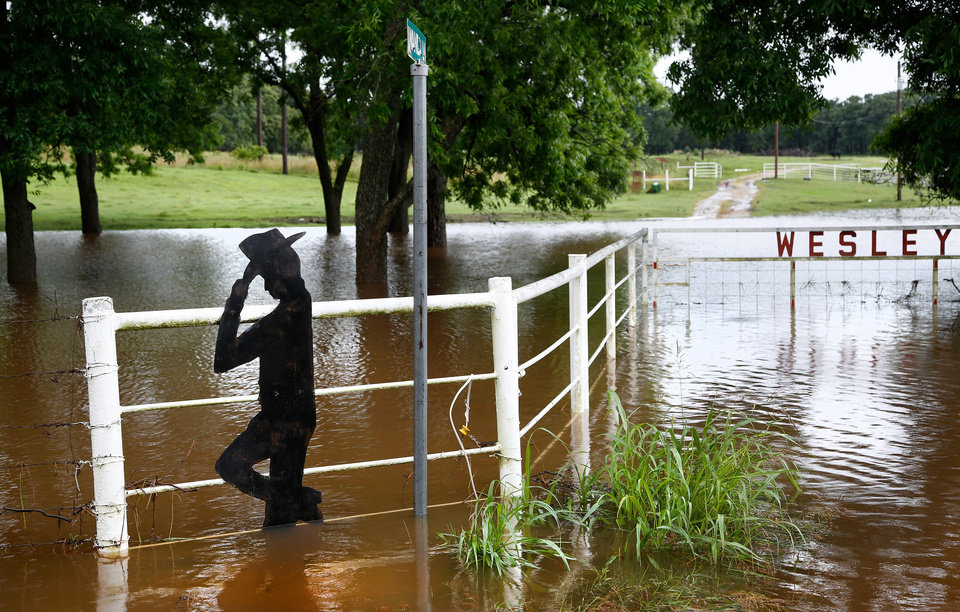 Photo - A decorative silhouette attached to  this fence on a farm on Hardesty Road, east of Coker Road in Shawnee, gives the appearance of a cowboy lifting his leg from a flooded field after rain from Hurricane Bill produced localized flooding in areas of Pottawatomie County on Thursday, June 18,  2015.   Photo by Jim Beckel, The Oklahoman.