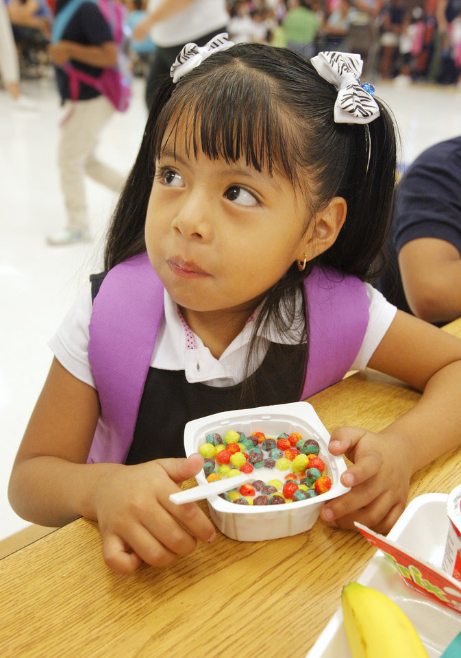 Photo - Kindergarten student Jennifer Bautista, age 5, eating breakfast in the school cafeteria before classes start for the day at Adams Elementary in Oklahoma City Wednesday, Aug. 1, 2012. Wednesday was the first day of classes in the Oklahoma City Public School District.  Photo by Paul B. Southerland, The Oklahoman
