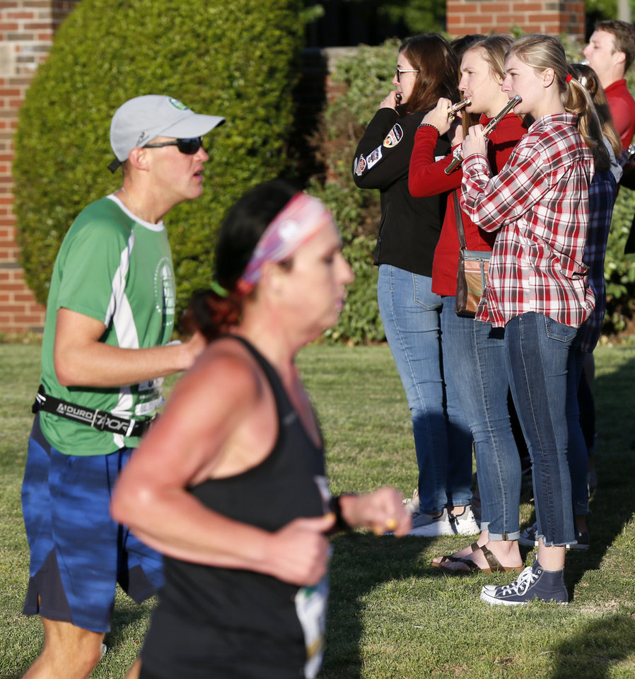 Photo - Members of the Pride of Oklahoma marching band play for runners at a water stop near the OU Medical Center on Lincoln Blvd. during the Oklahoma City Memorial Marathon in Oklahoma City, Sunday, April 28, 2019. [Nate Billings/The Oklahoman]