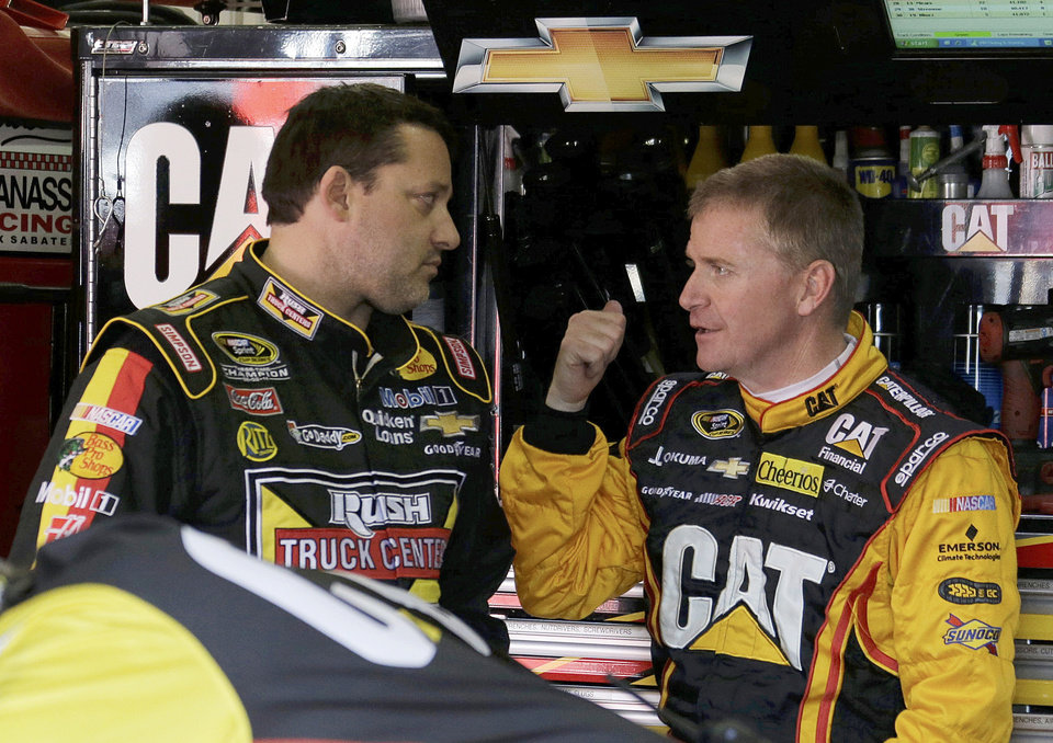 Photo - Defending champion Tony Stewart, left, and Jeff Burton chat before practice for the NASCAR Sprint Cup series Auto Club 400 auto race in Fontana, Calif., Friday, March 22, 2013.  (AP Photo/Reed Saxon)