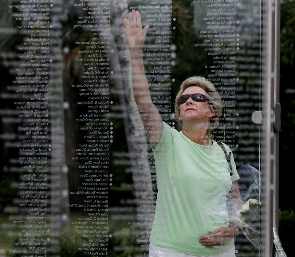 Photo - Kathy Maycen reaches to touch the name of her daughter, Lindsay Stapleton Morehouse, who was killed in the attack on the World Trade Center on Sept. 11, 2001, at a memorial in Palm Beach Gardens, Fla., Monday May 2, 2011.  Osama bin Laden, the face of global terrorism and architect of the Sept. 11, 2001, attacks, was killed in a firefight with elite American forces in Pakistan on Monday, then quickly buried at sea in a stunning finale to a furtive decade on the run. (AP Photo/The Palm Beach Post, Lannis Waters) ** MAGS OUT. TV OUT. NO SALES ** ORG XMIT: FLPAP101