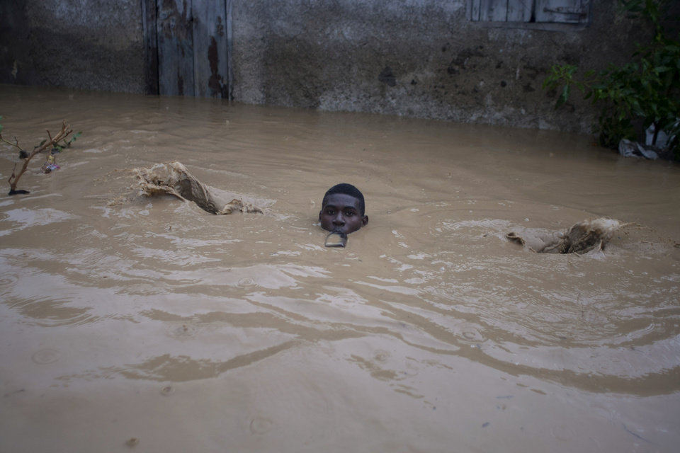 Photo -   A man carrying a bottle in his mouth slips as he wades through a flooded street, triggered by Tropical Storm Isaac, in Port-au-Prince, Haiti, Saturday, Aug. 25, 2012. Tropical Storm Isaac swept across Haiti's southern peninsula early Saturday, dousing a capital city prone to flooding and adding to the misery of a poor nation still trying to recover from the 2010 earthquake. (AP Photo/Dieu Nalio Chery)