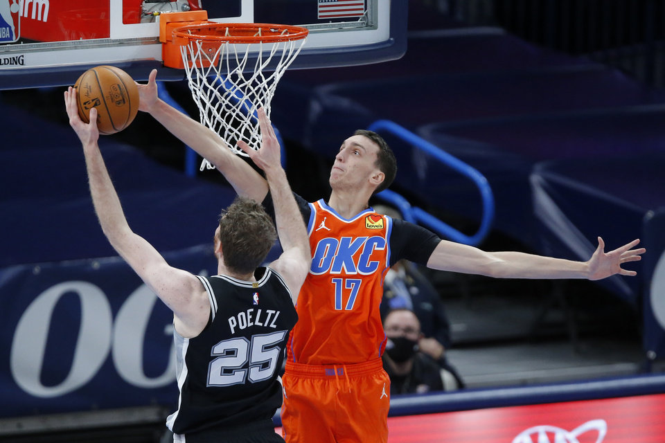 Photo - Oklahoma City's Aleksej Pokusevski (17) blocks the shot of San Antonio's Jakob Poeltl (25) during an NBA basketball game between the Oklahoma City Thunder and the San Antonio Spurs at Chesapeake Energy Arena in Oklahoma City, Tuesday, Jan. 12, 2021.  San Antonio won 112-102. [Bryan Terry/The Oklahoman]
