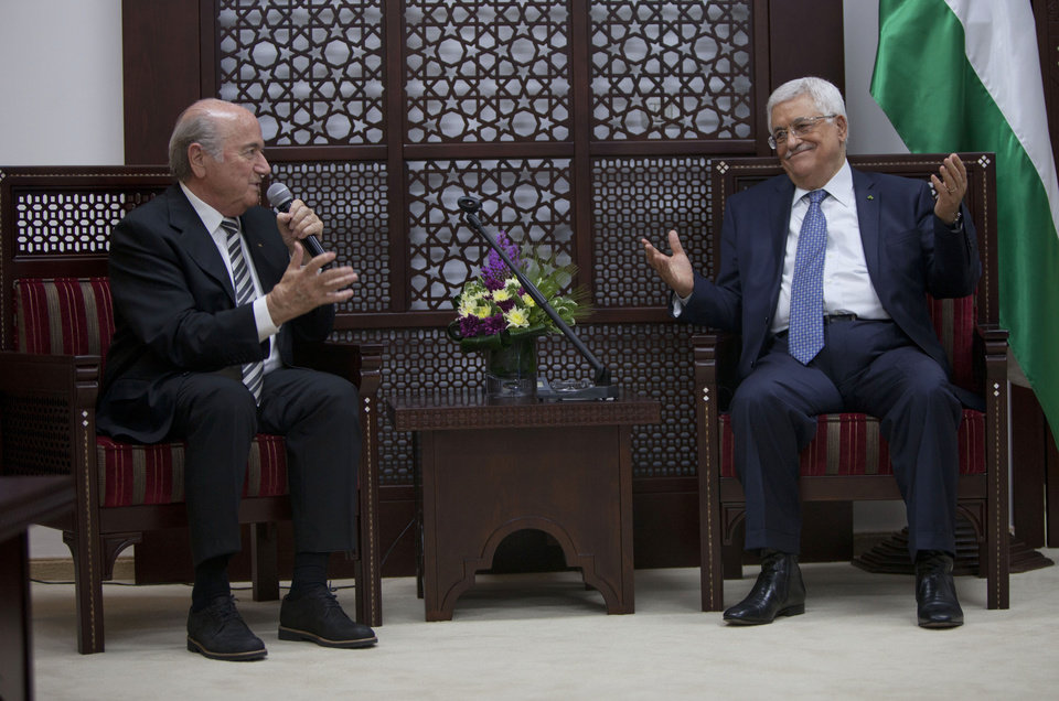 Photo - Sepp Blatter, President of FIFA, left, speaks during a meeting with Palestinian President Mahmoud Abbas at the presidential headquarters on the first day of his regional tour to Jordan, the Palestinian territories and Israel in the West Bank city of Ramallah, Monday, May 26, 2014. During an earlier press conference in Jordan Blatter said that his visit to Ramallah and Israel was to defend football in Palestine and also to defend football in Israel. (AP Photo/Majdi Mohammed)