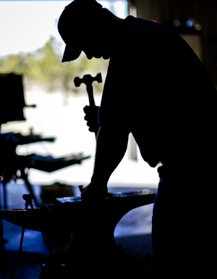 Photo - Mark Milster works at his shop in Goldsby. Milster's craftsmanship has taken him all over the world to learn and compete. He was recently inducted into the International Horseshoeing Hall of Fame.  Photo by Chris Landsberger, The Oklahoman   CHRIS LANDSBERGER - CHRIS LANDSBERGER