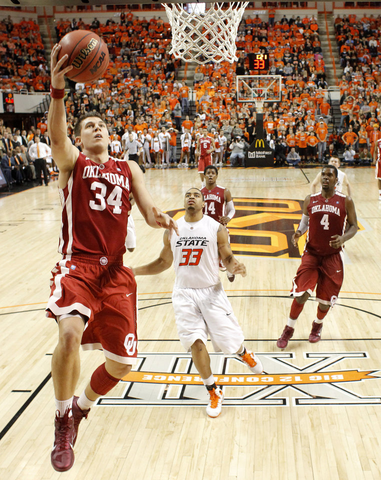 Photo - Oklahoma's Cade Davis (34) goes past Oklahoma State's Marshall Moses (33) to the basket during the Bedlam men's college basketball game between the University of Oklahoma Sooners and Oklahoma State University Cowboys at Gallagher-Iba Arena in Stillwater, Okla., Saturday, February, 5, 2011. Photo by Bryan Terry, The Oklahoman
