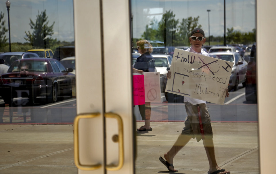 Photo -  Dillon Holt reflects in the glass door as he carries a sign during a protest Monday in Norman over a proposed rule change made by the Oklahoma Department of Mental Health and Substance Abuse Services in order to balance its budget. The cuts would affect private mental health providers and other agencies that provide mental health care.    CHRIS LANDSBERGER -  CHRIS LANDSBERGER