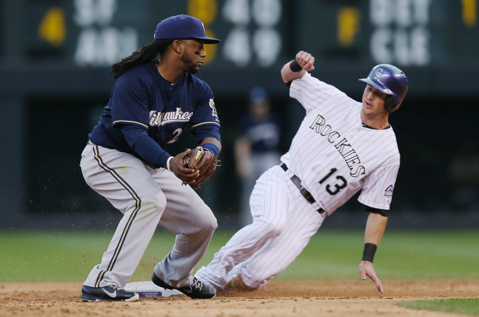Photo - Milwaukee Brewers second baseman Rickie Weeks, left, fields the throw as Colorado Rockies' Drew Stubbs steals second base in the third inning of a baseball game in Denver on Sunday, June 22, 2014. (AP Photo/David Zalubowski)