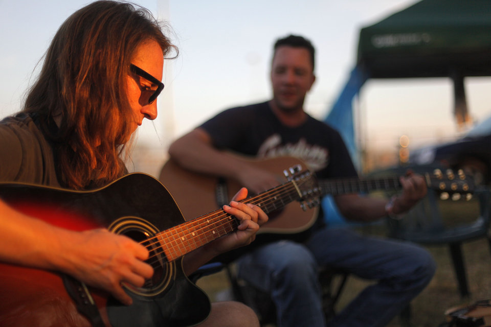 Photo - Mike Blackwell and Ross Johnson play music near their camp Thursday during the Woody Guthrie Folk Festival in Okemah. Photos by Garett Fisbeck, The Oklahoman