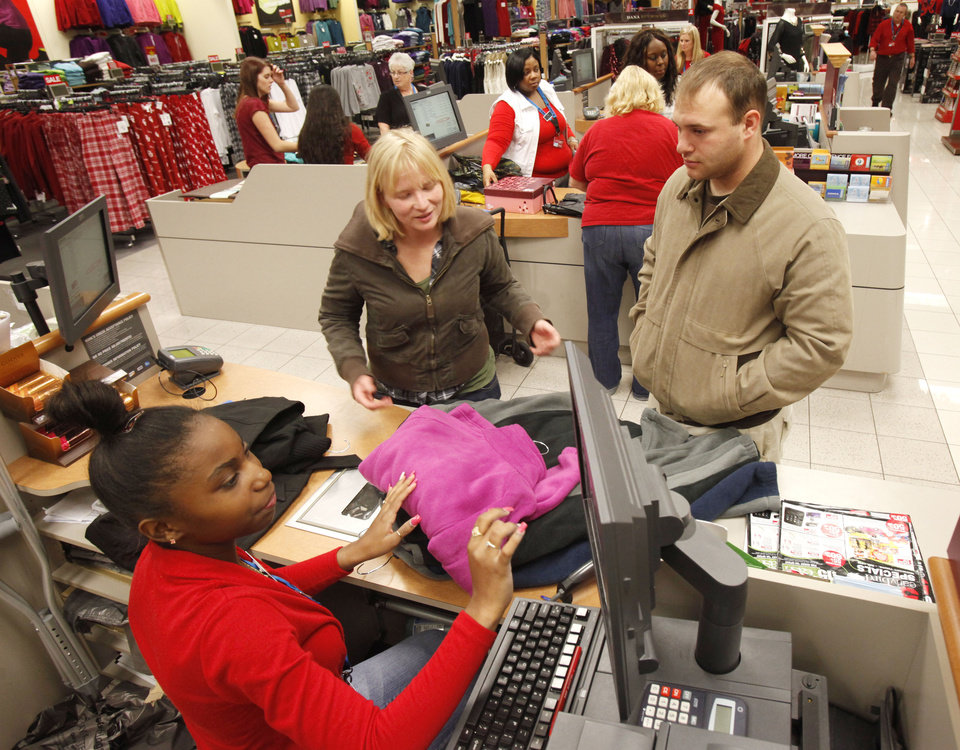Cashier Precious Turner rings up the purchases for customers Adam and Christy Tester during early morning Black Friday shopping at the Kohl's store in Midwest City, OK, Friday, November 23, 2012,  By Paul Hellstern, The Oklahoman