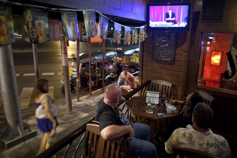 Photo - People look on at the Road House Bar Friday, Feb. 19, 2010, in Bangkok, Thailand, as golfer Tiger Woods addresses a gathering on live television.  (AP Photo/David Longstreath) ORG XMIT: DLL111