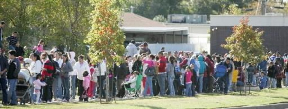 Photo - A long line that wrapped around a football field waits to receive their H1N1 vaccine at U.S. Grant High School in  Oklahoma City,  Oklahoma October 24, 2009. Photo by Steve Gooch
