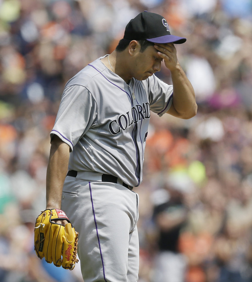 Photo - Colorado Rockies starting pitcher Jorge De La Rosa reacts after giving up a three-run home run to Detroit Tigers designated hitter Victor Martinez during the third inning of an interleague baseball game, Sunday, Aug. 3, 2014, in Detroit. (AP Photo/Carlos Osorio)