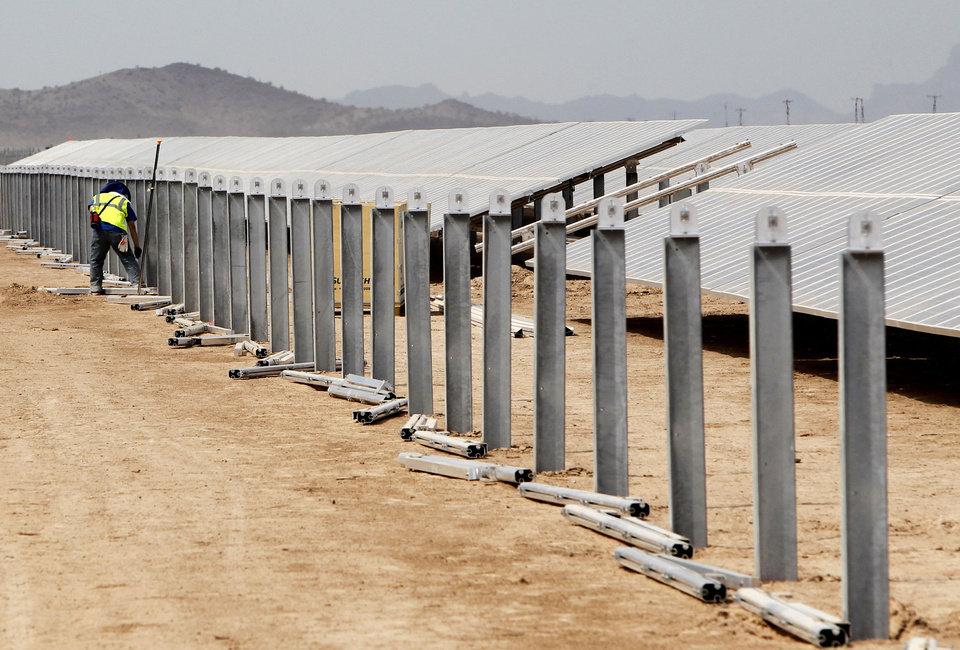 A worker stands near unfinished solar panel framework at a Mesquite Solar 1 facility under construction in Arlington, Ariz.  AP Photo