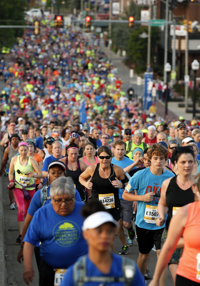 Photo - Runners make their way up the Dr. G.E. Finley Bridge as they run through Bricktown during the Oklahoma City Memorial Marathon in Oklahoma City, Sunday, April 24, 2016. Photo by Nate Billings, The Oklahoman
