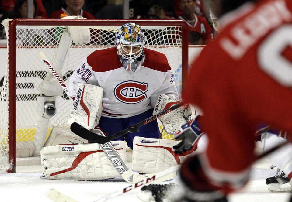 Photo - Montreal Canadiens goalie Peter Budaj (30) saves a shot by Chicago Blackhawks' Nick Leddy (8) during the second period of an NHL hockey game in Chicago, Wednesday, April 9, 2014. (AP Photo/Nam Y. Huh)