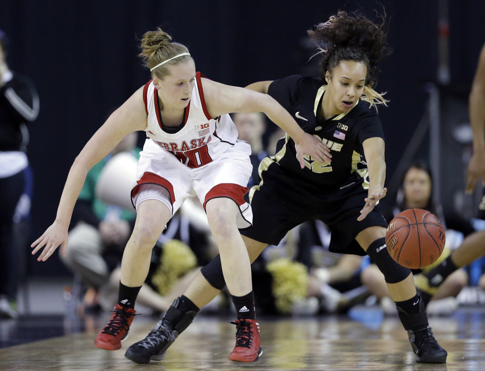 Photo - Purdue guard KK Houser, right, battles for a loose ball with Nebraska guard Lindsey Moore during the first half of an NCAA college basketball game in the Big Ten Conference tournament in Hoffman Estates, Ill., on Saturday, March 9, 2013. (AP Photo/Nam Y. Huh)