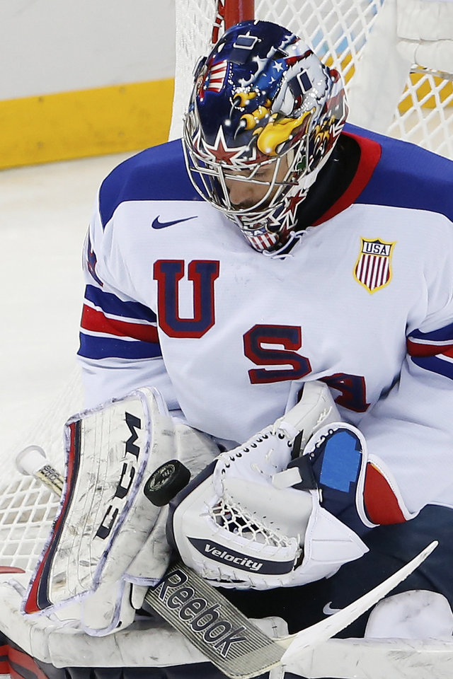 Photo - USA goaltender Ryan Miller blocks a shot on the goal during the 2014 Winter Olympics men's ice hockey game against Slovenia at Shayba Arena Sunday, Feb. 16, 2014, in Sochi, Russia. (AP Photo/Petr David Josek)