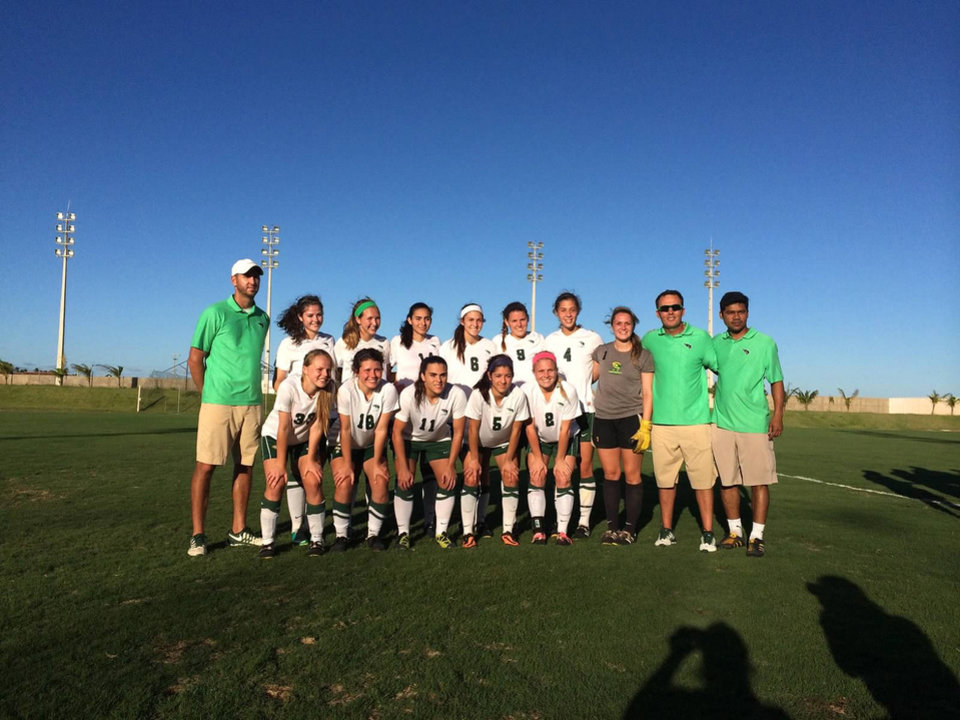 Photo -  The Oklahoma Baptist University women's soccer team, led by head coach Michael White and assistant coach Jeremy Hymel, pose for a picture before competing in a soccer game during the team's evangelism outreach trip to Brazil. Photo provided