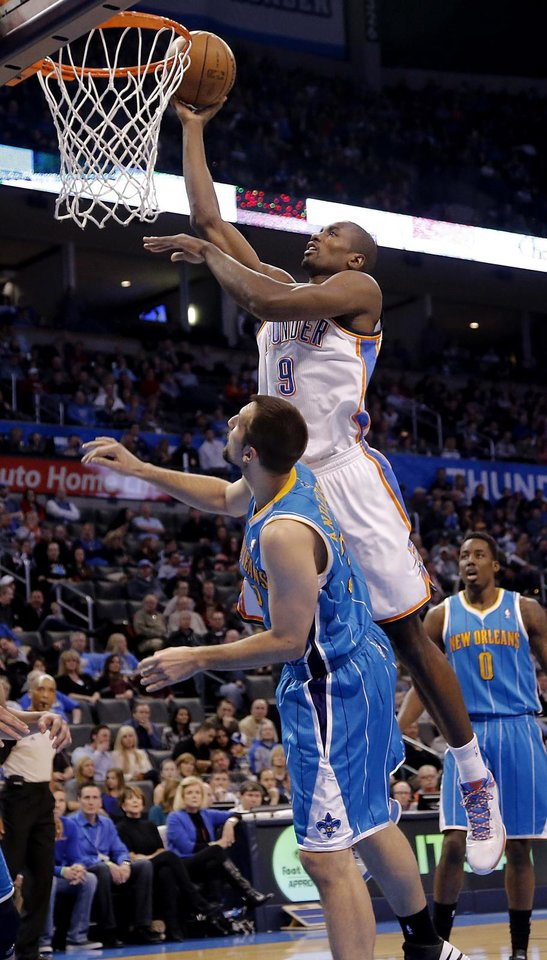Photo - Oklahoma City Thunder's Serge Ibaka (9) lays in a shot over New Orleans Hornets' Ryan Anderson (33) during the NBA basketball game between the Oklahoma City Thunder and the New Orleans Hornets at the Chesapeake Energy Arena on Wednesday, Feb. 27, 2013, in Oklahoma City, Okla. Photo by Chris Landsberger, The Oklahoman
