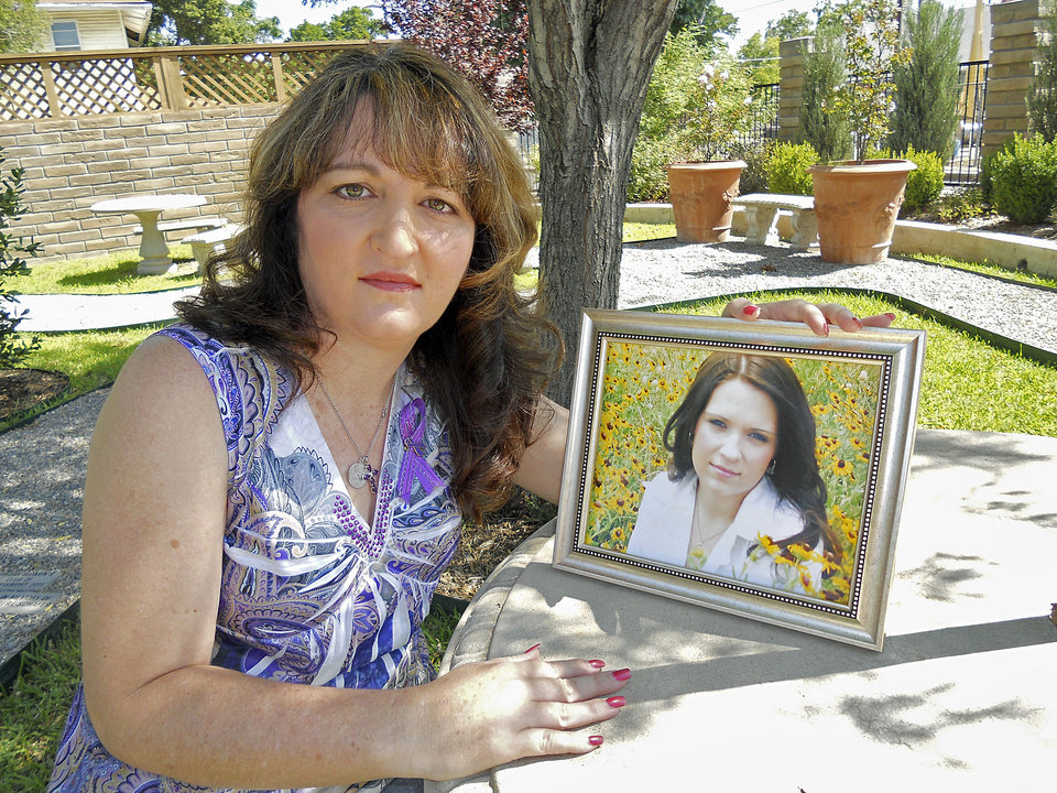 Tara Woodlee poses with a picture of her daughter, Ashleigh Lindsey, 20. >Lindsey was killed by her ex-boyfriend in July 2012 in Marshall County, >Okla.