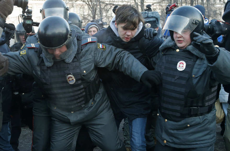 Police officers detain an opposition activist during an unauthorized rally in Lubyanka Square in Moscow, Russia, Saturday, Dec. 15, 2012. Thousands of opposition supporters gathered Saturday in central Moscow for an unauthorized rally to mark a year of a wave of massive protests against Vladimir Putin and the government. Several prominent opposition figures were detained in the course of the gathering, which was not sanctioned by authorities. (AP Photo/Misha Japaridze)