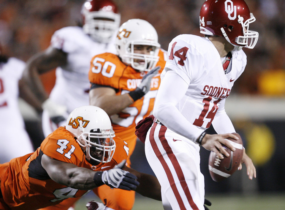 Orie Lemon of Oklahoma State dives for Sooner quarterback Sam Bradford during the first half of the college football game between the University of Oklahoma Sooners (OU) and Oklahoma State University Cowboys (OSU) at Boone Pickens Stadium on Saturday, Nov. 29, 2008, in Stillwater, Okla. STAFF PHOTO BY BRYAN TERRY