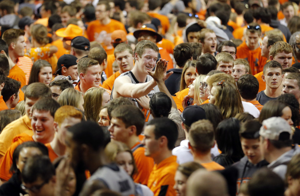 Photo - Oklahoma State's Mitchell Solomon (41) celebrates with fans following the men's college basketball game between Oklahoma State University and the University of Kansas at Gallagher-Iba Arena in Stillwater, Okla.,  Saturday, Feb. 7, 2015. OSU won 67-62. Photo by Sarah Phipps, The Oklahoman