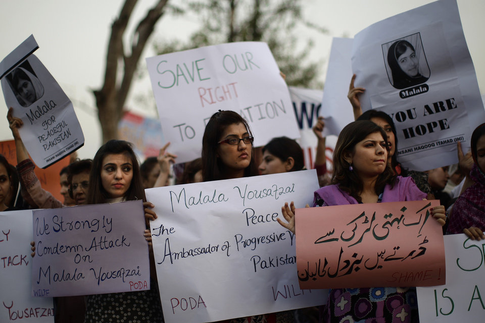 Pakistani women, hold banners during a protest condemning the attack on schoolgirl Malala Yousufzai, in Islamabad, Pakistan, Wednesday, Oct. 10, 2012. Pakistani doctors successfully removed a bullet Wednesday from the neck of a 14-year-old girl who was shot by the Taliban for speaking out in support of education for women, a government minister said. Banner bottom right reads,