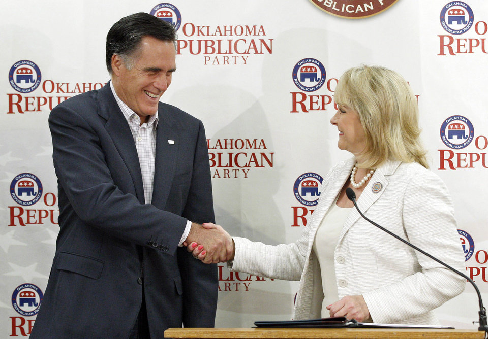 Photo - Republican presidential candidate, former Massachusetts Gov. Mitt Romney, left, and Oklahoma Gov. Mary Fallin, right, shake hands after she officially endorsed him during a speech to supporters at state Republican Party Headquarters in Oklahoma City, Wednesday, May 9, 2012. (AP Photo/Sue Ogrocki) ORG XMIT: OKSO103