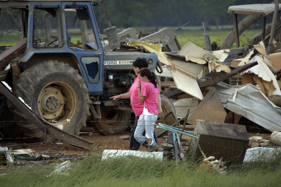 Photo - Residents survey the damage to a home near Bond, Miss., Wednesday, April 27, 2011. Several tornadoes hit  in the state resulting in number of deaths. (AP Photo/Rogelio V. Solis)