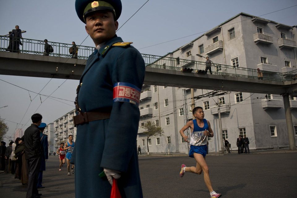 Photo - Runners pass under a pedestrian bridge in central Pyongyang during the running of the Mangyongdae Prize International Marathon in Pyongyang, North Korea on Sunday, April 13, 2014. The annual race, which includes a full marathon, a half marathon, and a 10-kilometer run, was open to foreign tourists for the first time this year. (AP Photo/David Guttenfelder)