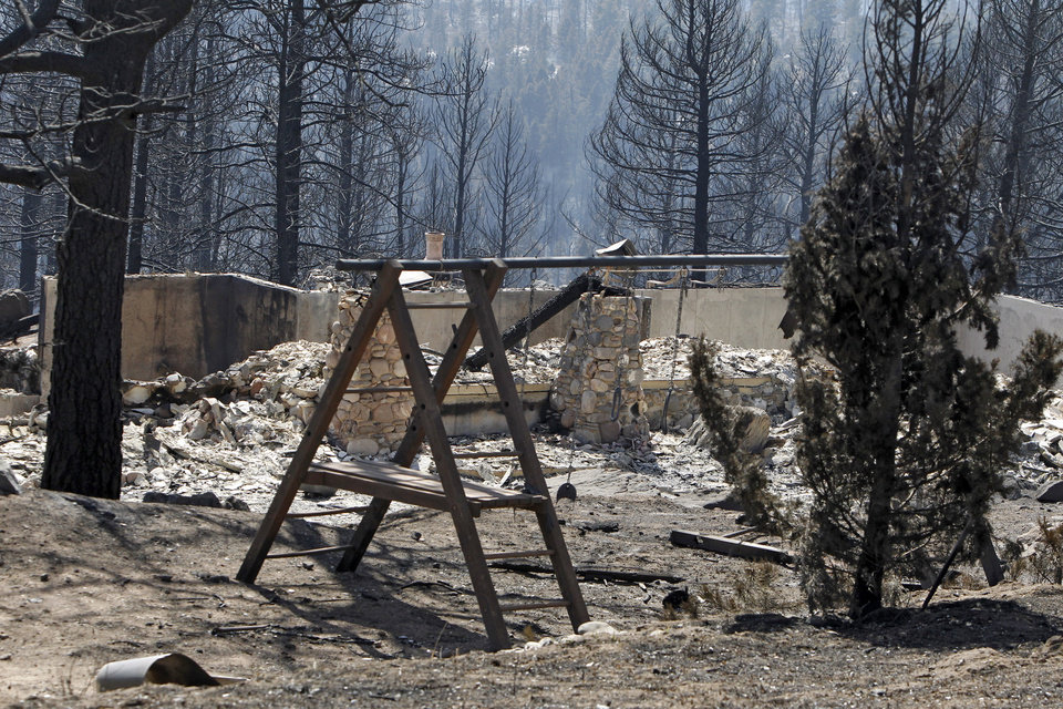 Photo -   The ruins of a home destroyed by a wildfire are framed by a child's swing set near Conifer, Colo., on Wednesday, March 28, 2012. Two people died in the wildfire that started Monday afternoon. (AP Photo/Ed Andrieski)