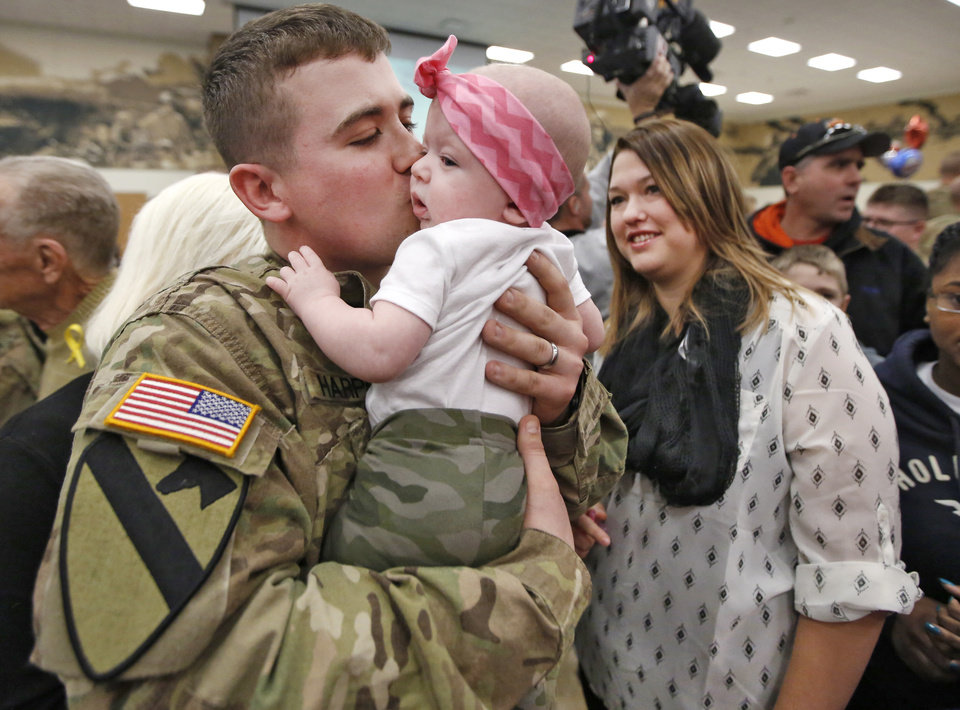 Photo - Spc. Justin Harper meets his daughter, Paisley, 4 months, for the first time, as his wife, Meagan Harper, watches. Paisley wore a special outfit for the occasion Friday in Mustang.  Photos By Steve Gooch, The Oklahoman  Steve Gooch -