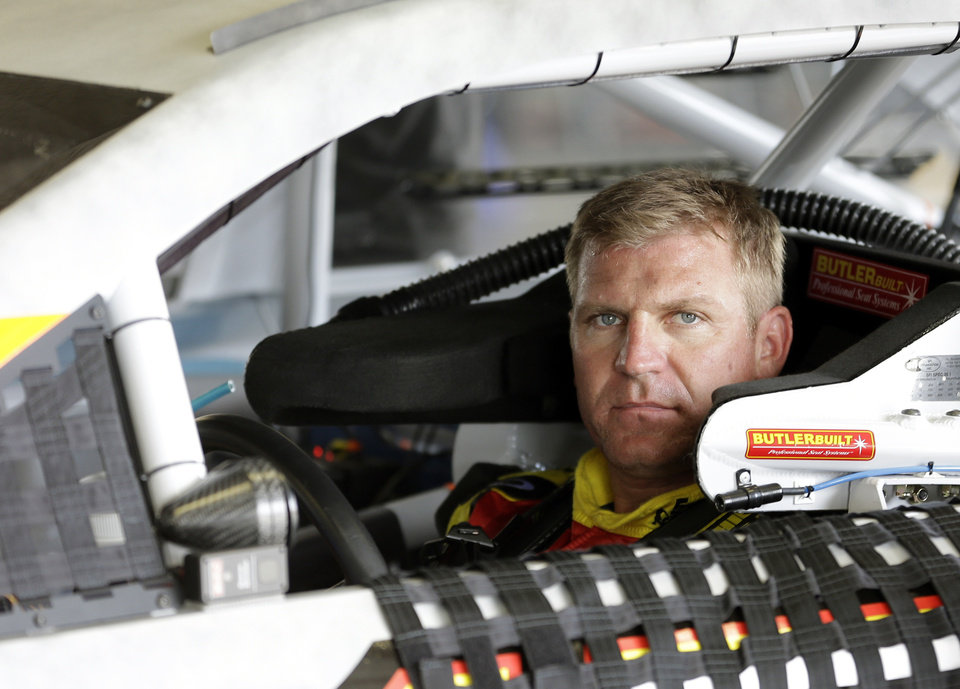 Clint Bowyer waits while crew members make adjustment to his car during NASCAR auto race testing at Daytona International Speedway, Thursday, Jan. 10, 2013, in Daytona Beach, Fla. (AP Photo/John Raoux)