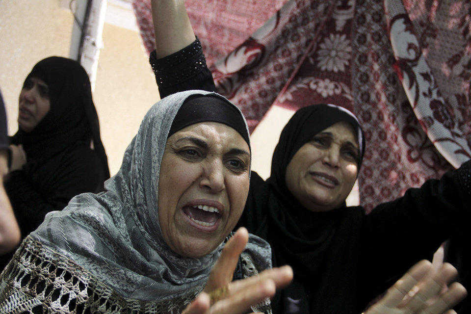 Photo - Palestinian relatives grieve during the funeral for a senior commander of the Hamas military wing, Mohammed Abu Shamaleh, who was killed in early morning Israeli strikes, at his family house in the Rafah refugee camp in the southern Gaza Strip, Thursday, Aug. 21, 2014. The pre-dawn strike leveled a four-story house in a densely populated neighborhood of Rafah, killing at least six people, including Abu Shamaleh and two other senior Hamas commanders. (AP Photo/Hatem Ali)