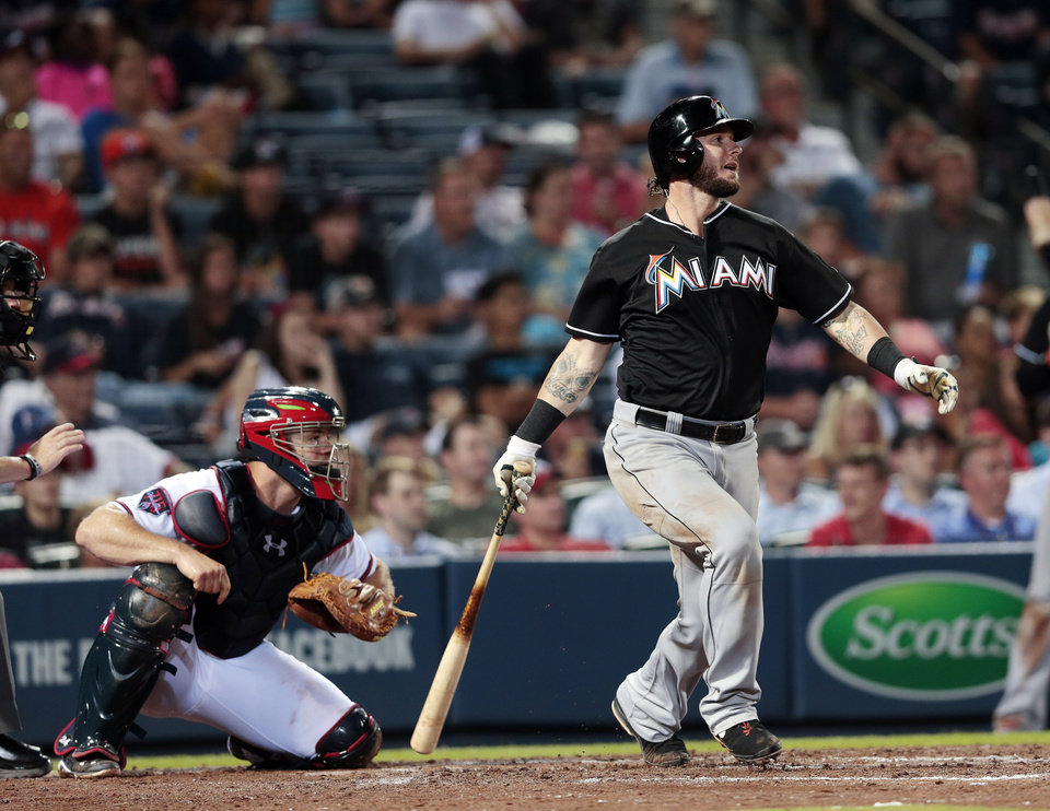 Photo - Miami Marlins' Jarrod Saltalamacchia, right, drives in the game-wining run with a base hit as Atlanta Braves catcher Evan Gattis looks on in the ninth inning of a baseball game on Thursday, July 24, 2014, in Atlanta. The Marlins won 3-2. (AP Photo)