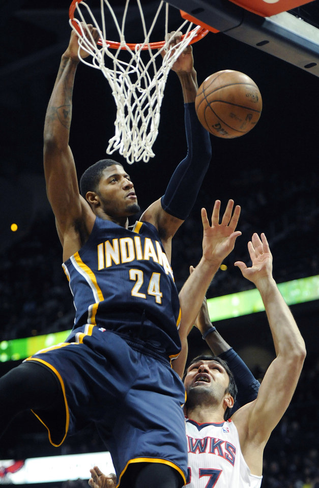Photo - Indiana Pacers forward Paul George (24) dunks over Atlanta Hawks center Zaza Pachulia during the first half of an NBA basketball game on Saturday, Dec. 29, 2012, at Philips Arena in Atlanta. (AP Photo/John Amis)