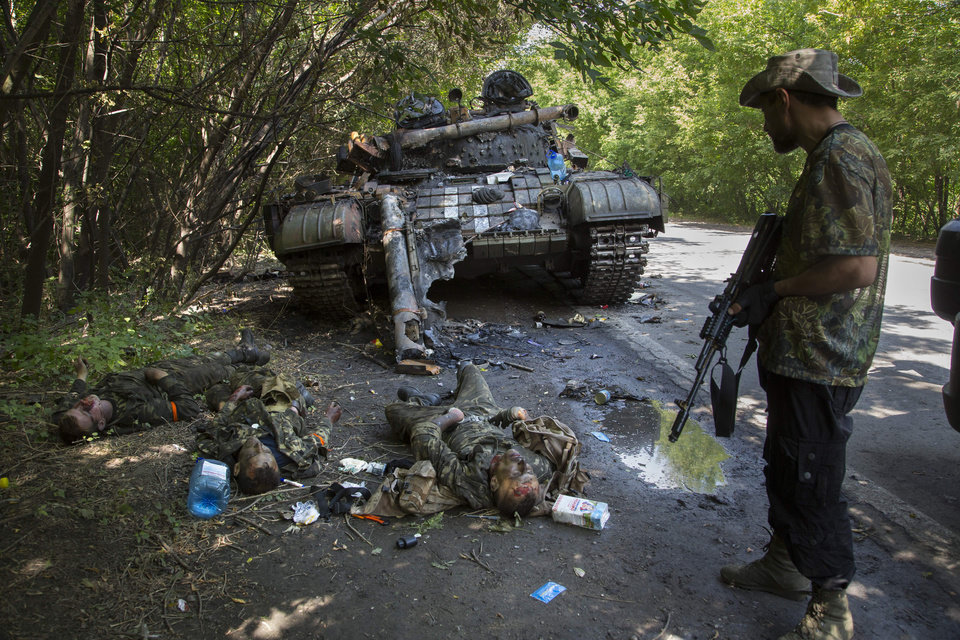 Photo - EDITORS NOTE GRAPHIC CONTENT - A pro-Russian fighter, right, stands next to bodies of crew members of destroyed Ukrainian tank in the northern outskirts of city of Donetsk, eastern Ukraine Tuesday, July 22, 2014. The soldiers were reportedly killed in fighting between rebels and government forces Monday. (AP Photo/Dmitry Lovetsky)