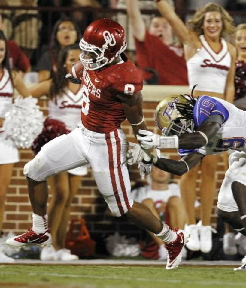 Photo - Oklahoma's Dominique Whaley (8) pushes Tulsa's Milton Howell (19) away and scores on a long run during the second half of the college football game between the University of Oklahoma Sooners ( OU) and the Tulsa University Hurricanes (TU) at the Gaylord Family-Memorial Stadium on Saturday, Sept. 3, 2011, in Norman, Okla. Photo by Steve Sisney, The Oklahoman ORG XMIT: KOD