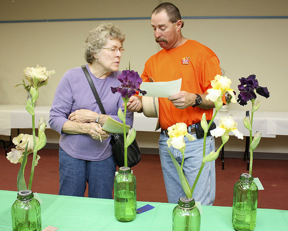 Mother and son Barbara and Rick Foale compare notes on their favorite irises at the Norman chapter's National Iris Society Show. PHOTO BY LYNETTE LOBBAN, FOR THE OKLAHOMAN <strong></strong>
