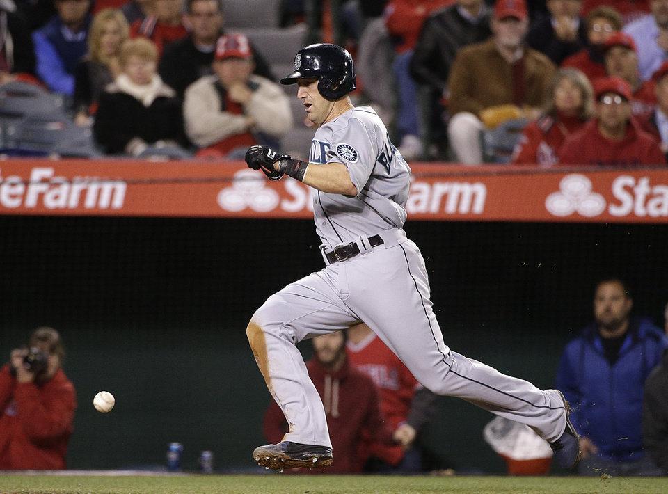 Photo - Seattle Mariners' Willie Bloomquist runs toward home plate to score on a single by Brad Miller as a wild throw from Los Angeles Angels' Josh Hamilton passes him during the fifth inning of a baseball game on Wednesday, April 2, 2014, in Anaheim, Calif. (AP Photo/Jae C. Hong)