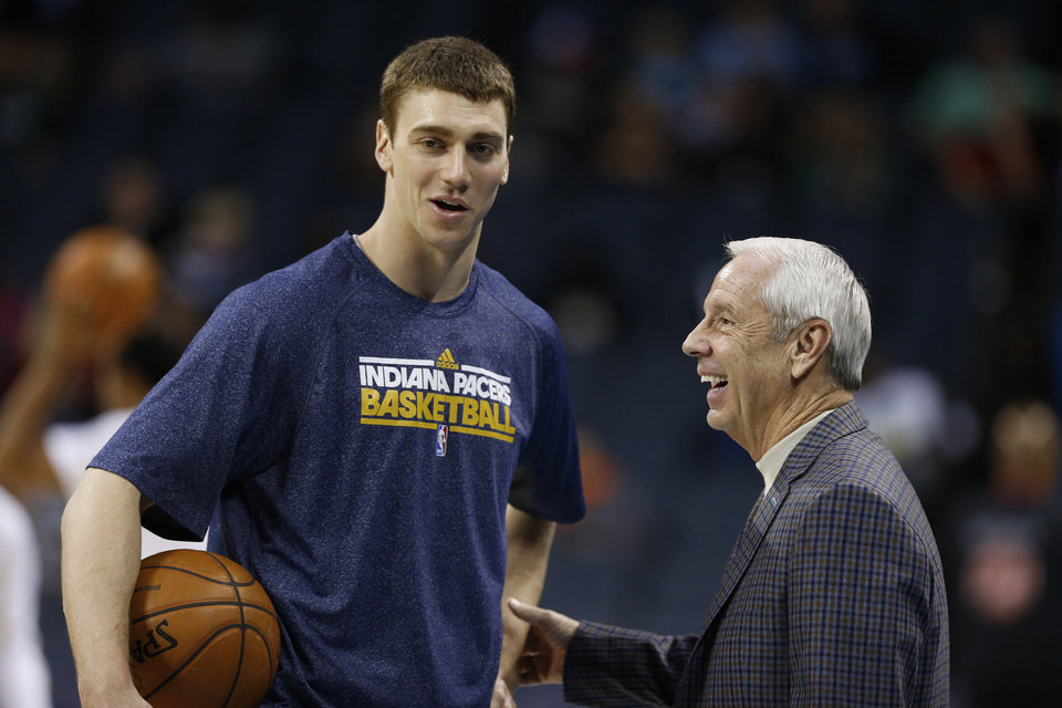 Indiana Pacers' Tyler Hansbrough, left, talks with North Carolina head coach Roy Williams, right, before an NBA basketball game between the Charlotte Bobcats and the Indiana Pacers in Charlotte, N.C., Tuesday, Jan. 15, 2013. (AP Photo/Chuck Burton)
