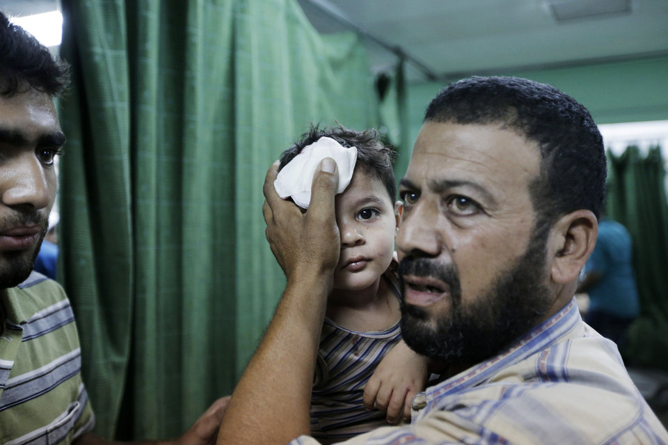 Photo - A Palestinian carries a boy, wounded in an Israeli strike at a house in Beit Lahiya, northern Gaza Strip, into the emergency room of the Kamal Adwan Hospital, in Beit Lahiya, Sunday, Aug. 3, 2014. (AP Photo/Lefteris Pitarakis)