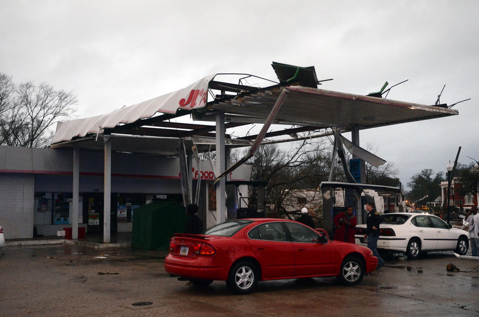 Photo - Hattiesburg Police officers talk to onlookers at a damaged gas station in Hattiesburg, Miss. after an apparent tornado that moved through area on Sunday, Feb. 10, 2013. (AP Photo/The Hattiesburg American, Bryant Hawkins)