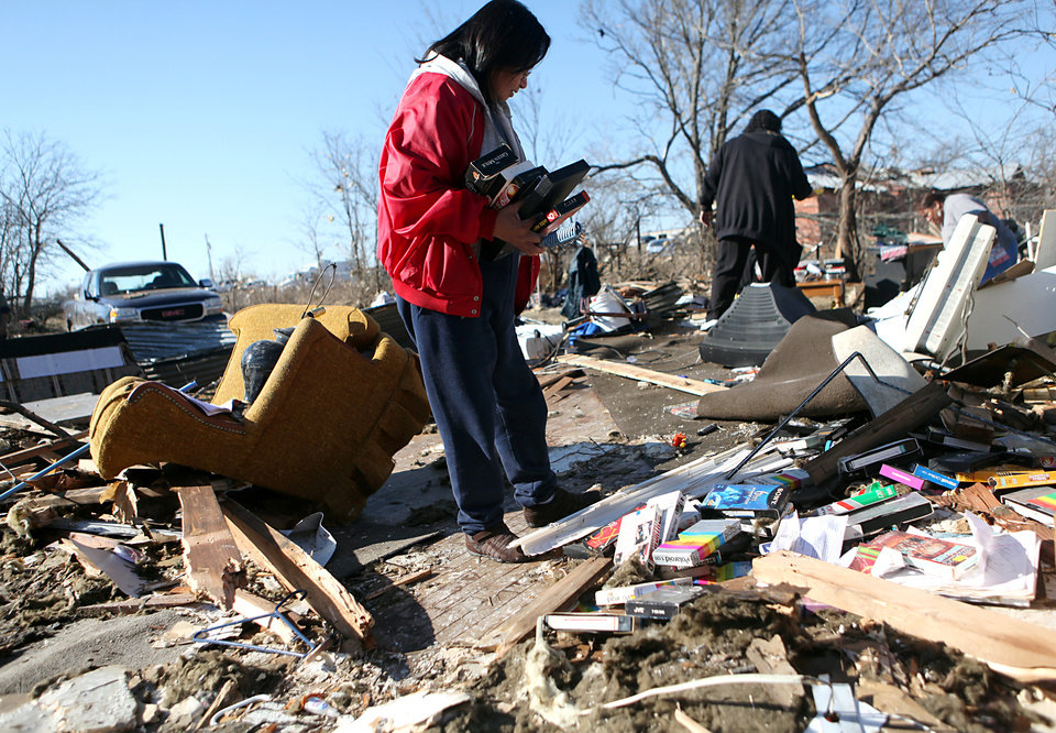 Photo - Shirley Mose looks through the debris of her home following deadly storms around Lone Grove, Okla., Feb. 11, 2009. By John Clanton, The Oklahoman