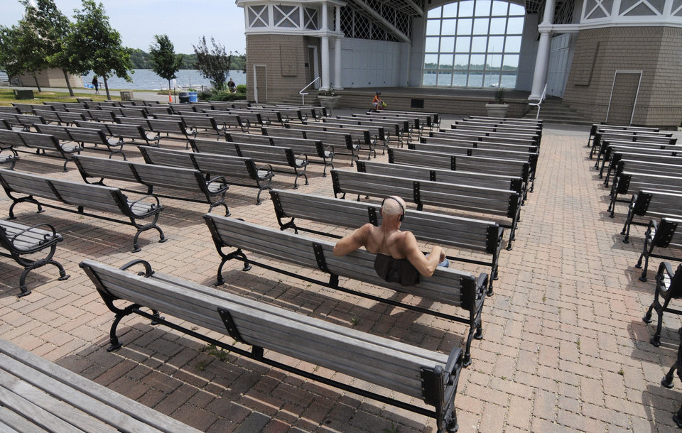Photo -   A man has the Lake Harriet Bandshell seats to himself Friday, July 6, 2012 in Minneapolis where temperatures reached into the upper 90's for another day during the heat wave. The National Weather Service said the record-breaking heat that has baked the nation's midsection for several days was slowly moving into the mid-Atlantic states and Northeast. (AP Photo/Jim Mone)
