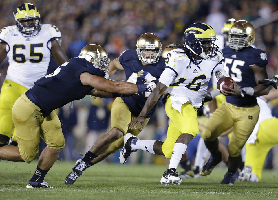 Photo -   Michigan's Denard Robinson runs out of the tackle of Notre Dame's Manti Te'o (5) during the first half of an NCAA college football game Saturday, Sept. 22, 2012, in South Bend, Ind. (AP Photo/Darron Cummings)